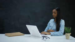 4K Woman working on laptop computer with blank chalkboard background Stock Footage