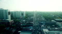 Aerial tracking shot over a busy city street with several destroyed buildings. Stock Footage