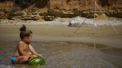 Outdoor portrait of a little girl with a watermelon on the sea shore Stock Footage