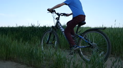 Boy in hat rides a bicycle on the nature of the evening  slow motion back view Arkistovideo