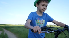 Boy in hat rides a bicycle on the nature of the evening  slow motion Arkistovideo