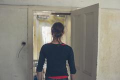 Woman standing by door in house being renovated - stock photo