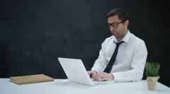 4K Pensive businessman working on laptop with chalkboard background Stock Footage