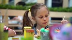 Little girl paints ceramic cat at the table Stock Footage