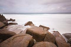 Long exposure with granite boulders at Anse Bazarca in the south of Mahe, Sey Stock Photos