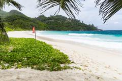 Red flag due to high surf at Anse Intendance in the south of Mahe, Seychelles - stock photo