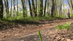 Girl riding fast a bike in the woods. Slow motion Stock Footage