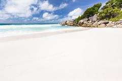 Perfect white beach Petite Anse in La Digue, Seychelles with granite boulders - stock photo