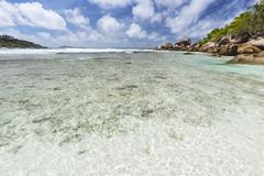 Shallow water and corals at Anse Cocos in La Digue, Seychelles Stock Photos