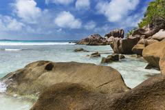 Shallow water and granite at Anse Cocos in La Digue, Seychelles Stock Photos