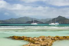 Perfect white beach in La Digue, Seychelles protected by a row of boulders le Stock Photos