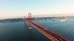 Flying over the Bridge Ponte 25 de Abril on the Tagus river in Lisbon at morning Stock Footage