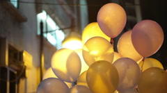Helium gas colourful party balloons at night with back light - stock footage