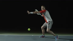 A man playing tennis front shot, on a court at night Stock Footage