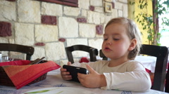 Little child using smartphone, watching the movie and refusing the food. Stock Footage