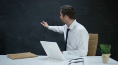 4KBusinessman with laptop moving his hand as if writing or drawing on chalkboard Stock Footage