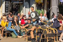 Parisians and tourists enjoy food and drinks in cafe sidewalk in Paris - stock photo