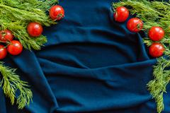 Cherry tomatoes over blue textile with copy space - stock photo