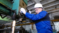 Man drilling with a machine making a hole in a steel bar Stock Footage