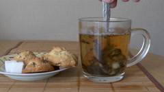 Male hand stirring a cup of tea. Sugar and oatmeal cookies Stock Footage
