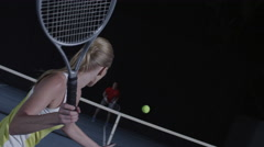 Woman tennis swing, male opponent in soft focus on the other side of the court Stock Footage
