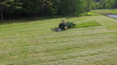Man on Green John Deer Tractor Cutting Grass Stock Footage