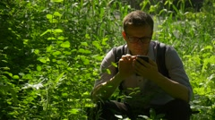 Backpacker Squatting on a Ground in Park Holding Phone Green Lush Grass Bushes Stock Footage