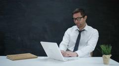 4K Portrait smiling businessman using laptop on blank chalkboard background Stock Footage