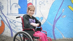 Girl disable on a wheelchair smiling with brush in hand - stock footage