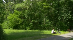 Man Cyclist Sitting in Park and Talking on Phone Spend Time at the Nature Fresh Stock Footage