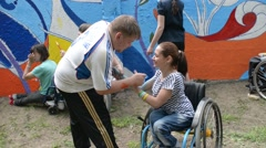 Man draws in blue a hand of a girl disabled on wheelchair - stock footage