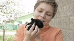 Girl holds and pets little baby black rabbit Stock Footage
