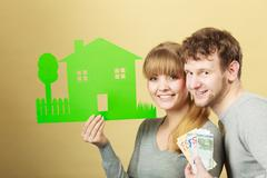 Wife and husband holding paper house. - stock photo