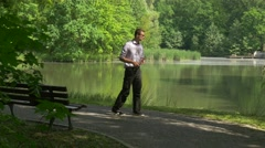 Man With Virtual Tablet Walks by Park Businessman at the Nature Forex Trading Stock Footage