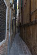 Very narrow old, vintage street in Venice. Curvy narrow road in Venice - stock photo