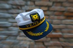 Levitating Venezia navy hat in front of blurred brick wall with zoom effect. - stock photo