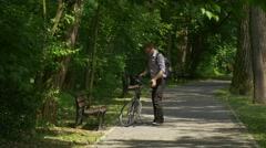 Man Gets on a Bicycle Riding in Green Park Cyclist Sportsman Young Man in - stock footage