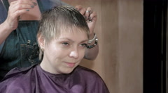 Hairdresser cuts combs and styles woman's hair - stock footage