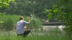 Man With Mobile Phone Throws a Stone Into Lake Green Park Gets up Holding a Stock Footage