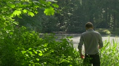 Tourist Keeps Hands Behind the Head Resting Standing Under the Maple Lush Stock Footage