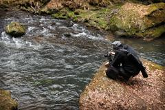 outdoor-photographer at work capturing a wild river - stock photo