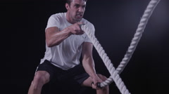 Tilt up to a closeup of a man's face working out with Battle Ropes Stock Footage
