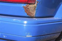 Closeup of Severe Rust and Damaged Bumper on Vehicle - stock photo