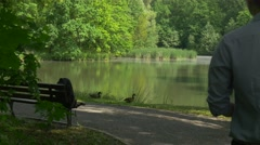 Man Comes to Rest in Park Looking at Wild Ducks Sits Down to the Bench by Lake Stock Footage