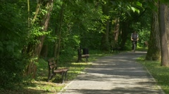 Backpacker is Riding a Bicycle Stops at the Bench in Park Alley Gets Off His - stock footage