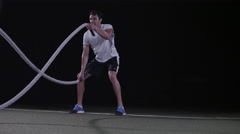 Wide shot of a man working out with Battle Ropes on an artificial turf field Stock Footage