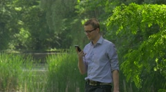 Man Types a Number Talking on Smartphone in Park Clicks Mobile Phone Spend Time Stock Footage
