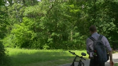 Cyclist Gets on the Bicycle Riding by Park Nature Fresh Green Trees Sunny Stock Footage