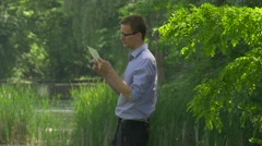 Businessman Clicks Virtual Tablet in Summer Park Forex Internet Shopping Stock Footage