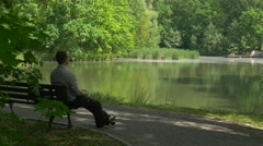 Man Resting on a Bench Makes a Call on Phone Park Alley by the Lake Tourist is Stock Footage